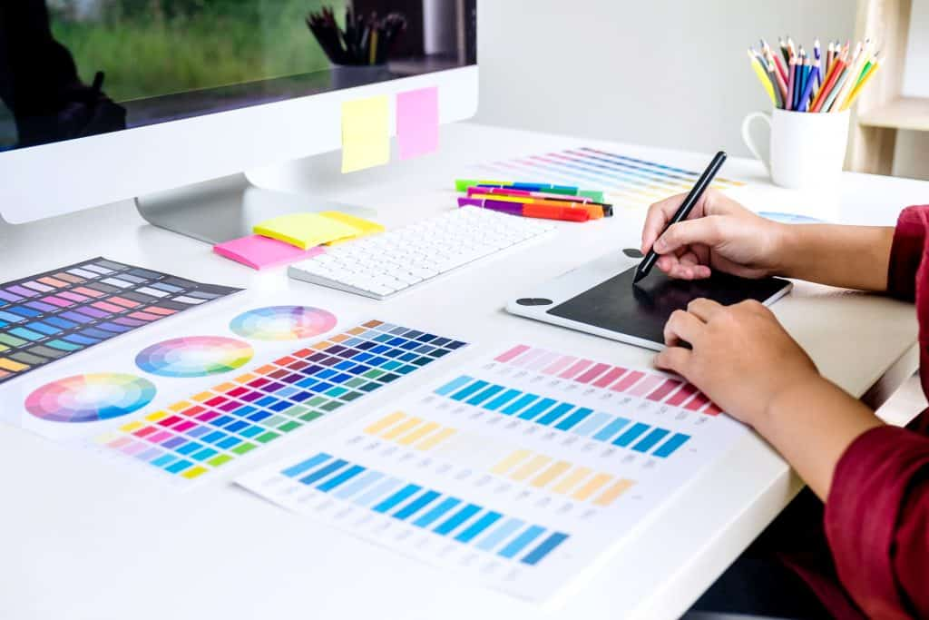 Image of female creative graphic designer working on color selection and drawing on graphics tablet at workplace.